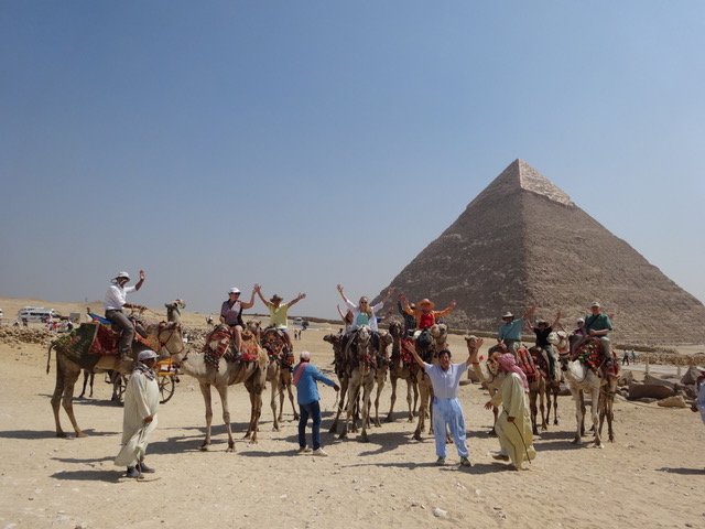 Ancient Legacies: Egypt participants pose on the backs of camels in front of the pyramids